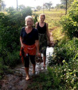 Petra und Jette auf dem Weg zum Gottesdienst - barfuß durch den Bach